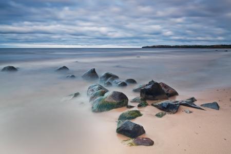 Pedras molhadas no lago de surf na praia da areia A exposição longa
