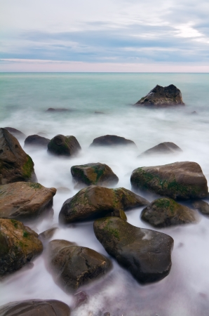 Wet stones in the surf with long exposure Stock Photo