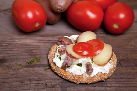 Toast with surstromming and tomatoes on the wood table Stock Photo - 16058966