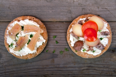 Two sandwiches with Swedish herring on the wooden table
