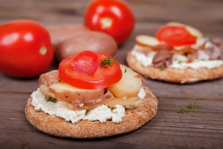 Two sandwiches with herring, potato and tomatoes on the table