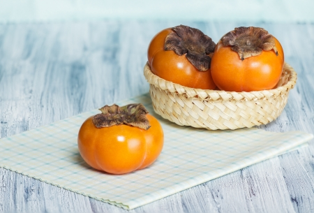 Two persimmons in the basket and one on the table Stock Photo - 16748833