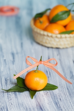 One mandarin against the basket  Placed on the leafs  Roll of tape on the background