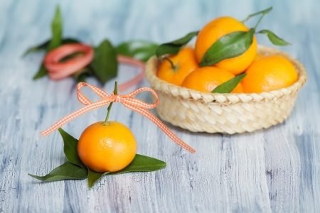 One mandarin near the basket with other mandarins  Roll of tape on the background