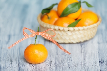 One mandarin with  colored tape bow-knot  Some mandarins in the basket on the background Stock Photo - 16748829