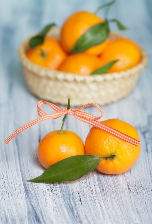 Two mandarins on the old blue-white table near the basket with mandarins