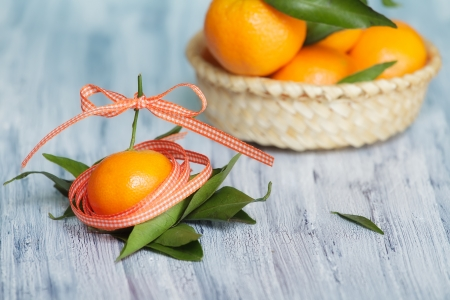 One mandarin in the colored tape  Some mandarins in the basket on the background Stock Photo