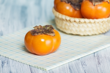 Three persimmons on the table  One on the napkin and two in the basket