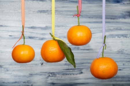 Four mandarins are hanging  on the colored tapes against old blue-white board Stock Photo