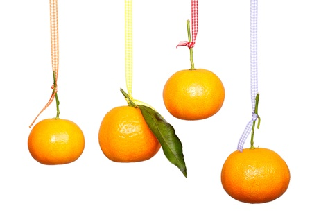 Four mandarins are hanging on the colored tape against the white background. Isolated. Stock Photo