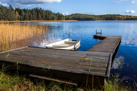 Blue lake with boat at the pier Stock Photo