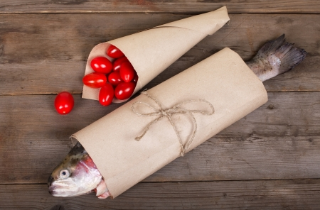 Fresh salmon with small tomatoes in the paper-pack