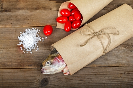 Fresh salmon in the paper-bag with tomato and salt