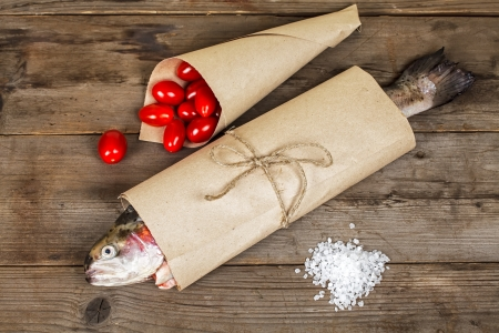 Fresh salmon in the paper-bag with salt and tomato Stock Photo