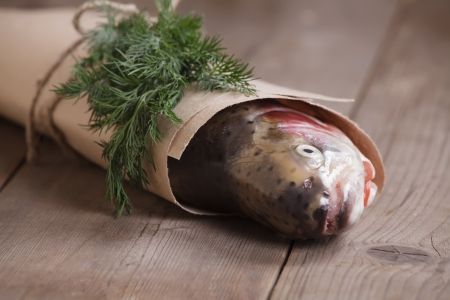 Fresh salmon in the paper-bag with a piece of greenery