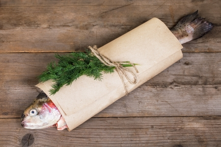 Fresh salmon on in the paper-bag on old wooden table Stock Photo