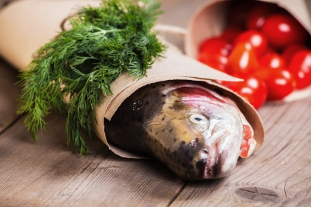 Fresh salmon in the paper with a pice of greenery and some small tomatoes Stock Photo - 17446256