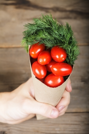 Small paper-bag with tomatoes in the hand  Top view