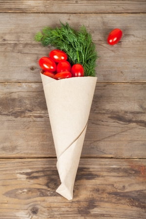 Small red tomatoes in the paper-bag with a piece of greenery Stock Photo