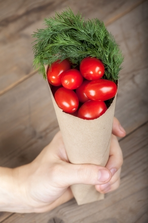 Small paper cornet with greenery and tomatoes in the hand