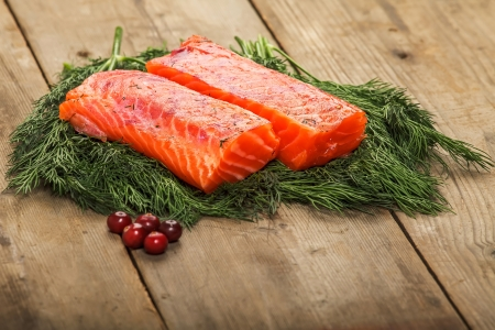 Two pieces of salty salmon over the greenery on the table with some cranberry