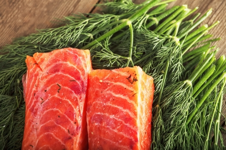 Two big pieces of gravlax on the table over greenery Stock Photo