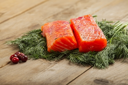 Two pieces of salty salmon with greenery and cranberry on the old wooden table