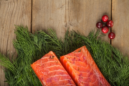 Two pieces of gravlax with a piece of greenery and some cranberry