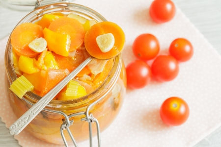 Glass jar with vegetables ragout and cherry tomatoes on the napkin