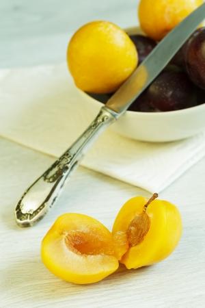 Ameixa amarela Cuted e bacia com ameixas no fundo Imagens