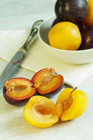 Two cuted different varieties of ripe plums photo