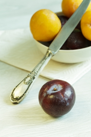 Purple plum and bowl with plums at the background