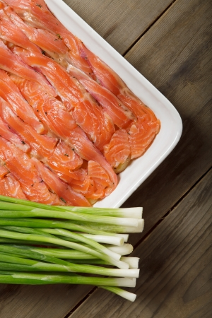 The dish for baking with thin slices of salmon and spring onions Stock Photo