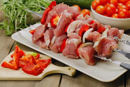 Raw shashlik - marinated meat for roasting on a skewers, with tomatoes, bell pepper and greenery