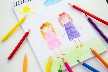 Pencil or pencil as a child`s hand drawn friends, grass, colorful sun. Children paint racism, friendship with a black man and a disabled person in a wheelchair.
