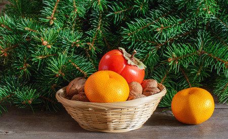Fir branches, wicker vase with tangerines and nuts on the wooden background