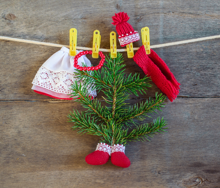 Christmas tree, rope, clothespins, boots, hat, scarf and red beads on the wooden background