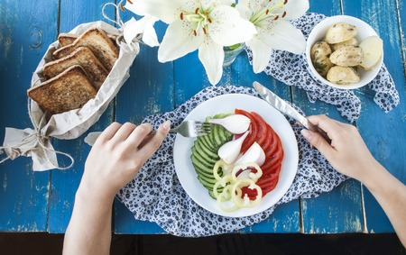 Breakfast with vegetables, womens hands,