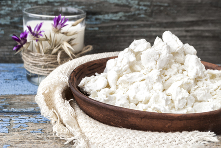 milk products: Cottage cheese in a clay plate, glass with milk on a wooden background.