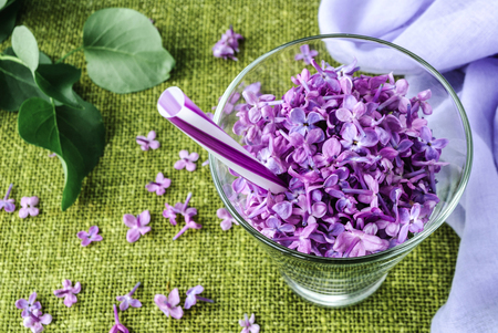 oncept: lilac flowers in a glass of cocktail, close-up Stock Photo