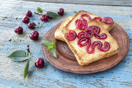 Toast with cherry jam on a wooden table
