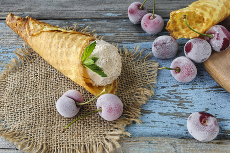 Wafer horn with ice cream and frozen berries on a wooden surface