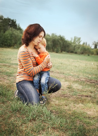 Mom and his little son are hugging on the background of a green glade. Reklamní fotografie