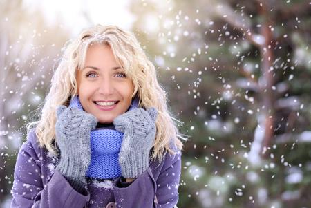beautiful blonde woman walking outdoors under snowfall Reklamní fotografie