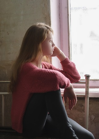Depressed young girl sitting in the abandoned building. Foto de archivo