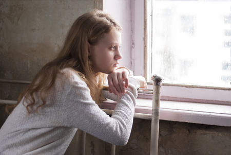 Depressed young girl sitting in the abandoned building. Stock Photo