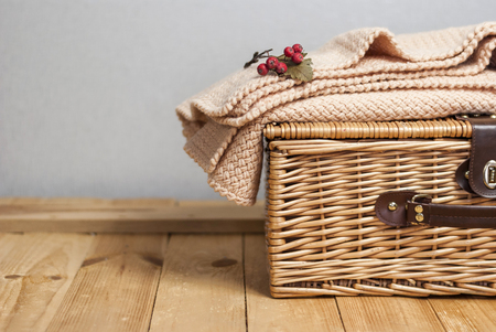 a picnic basket with knitted plaid on wood surface