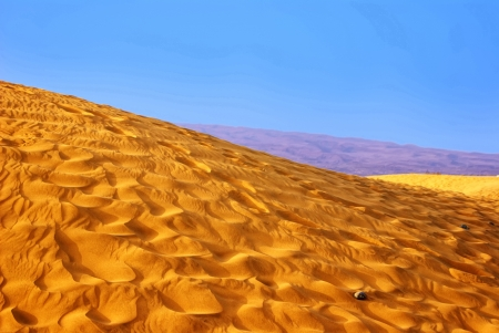 Sand Dunes Landscape with lilac mountains at the horizon Stock Photo