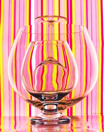 overturned: Glasses of different sizes standing straight and overturned on colourful striped background