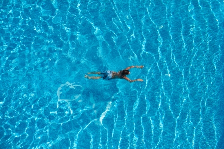 A boy is swimming in a pool with blue water  Top view  Stock Photo - 21698969